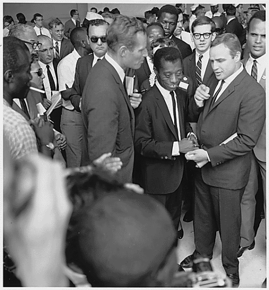 Charlton Heston, James Baldwin, and Marlon Brando at the March on Washington in 1963. Sidney Poitier is in the background, and Harry Belafonte is standing behind Brando (USIA photo, via Wikimedia Commons)